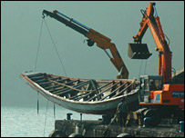 Crane lifting migrant boat from the sea