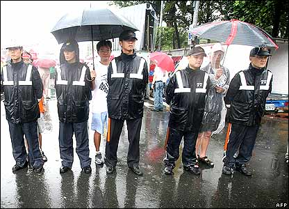 Protesters offer to shield police from the rain.