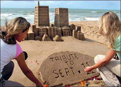 Well-wishers place flowers at a sand replica of the World Trade Center