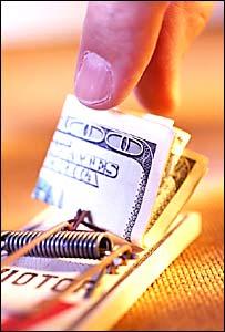 Una mano toma un billete de una ratonera
