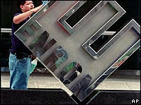 Man polishing sign outside Enron's headquarters in 2001