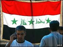 Men walk in front of Iraqi flag