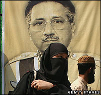 A Pakistani woman passes a portrait of President Pervez Musharraf