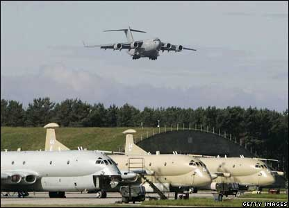 The C17 transport aircraft bearing the bodies comes in to land above a fleet of Nimrods at RAF Kinloss
