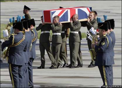 The coffin containing Joseph Windall of the Royal Marines is carried from the transport aircraft