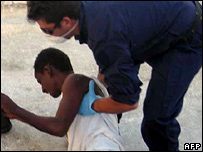 Italian Coast Guard official helps would-be illegal immigrant at port of Lampedusa
