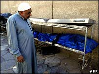 Man looks at covered bodies at a Baghdad hospital on 12 September