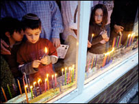 Jewish boy lights a candle for Hanukah