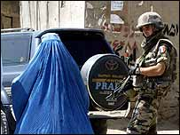 Afghan woman passes French Isaf soldier in Kabul