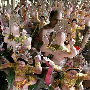 An artisan gives final touches to an idol of Hindu God Vishwakarma in Gauhati, India