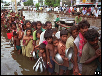 Flood victims queue for food aid (Image: AP)