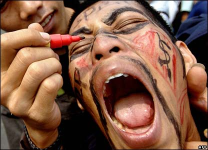 An Indonesian worker has his face drawn on as he shouts during a protest in Jakarta