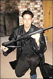 El tirador en una foto con un arma y vestido de negro