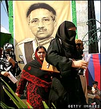 Women pass a poster of President Musharraf