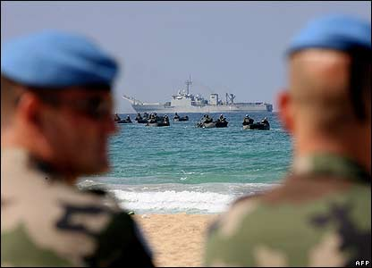 Two UN peacekeepers look on as Spanish troops land on a beach in Tyre, southern Lebanon