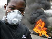 Abidjan toxic waste protester in front of burning barricades