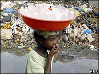 Water seller holds her nose near waste dump in Abidjan
