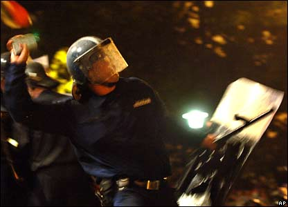 A Hungarian riot police officer throws a stone back to demonstrator