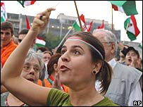 Hungarians wave national flags and shout anti-government slogans in a demonstration outside parliament in Budapest, Hungary, on Monday