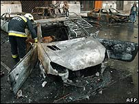 Hungarian firefighters examine wrecks of burned cars in front of the national TV headquarters