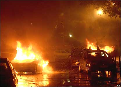Cars on fire outside the headquarters of state television in Budapest