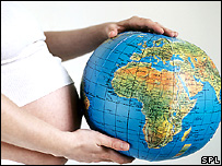 Pregnant woman holding globe (CRISTINA PEDRAZZINI/SCIENCE PHOTO LIBRARY)