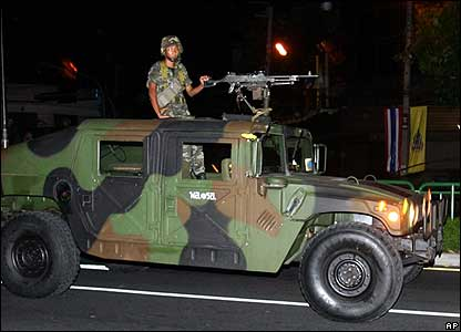 Thai soldiers stand guard in a military car next to Government House in Bangkok