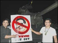 Supporters of the coup d'etat stand in front of a military tank in Bangkok