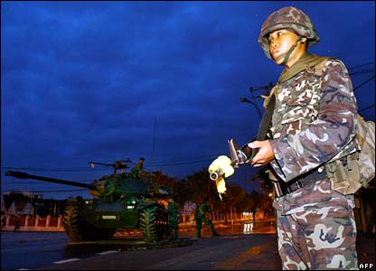 A Thai soldier stands guard next to a tank at dawn near the Government House in Bangkok