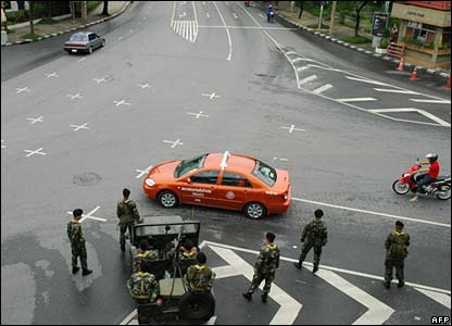 Thai army soldiers monitor roads linking to the Government House building in Bangkok