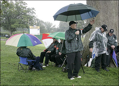Course officials take shelter from the wind and rain