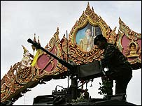 A tank passes under a decorative archway featuring a portrait of the revered Thai king