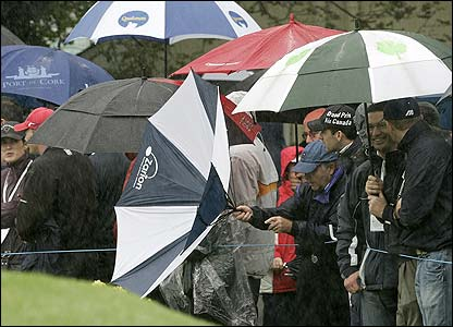 A spectator struggles with his umbrella in the strong wind