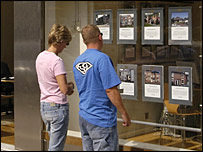 Couple looking at properties in estate agent's window