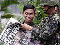 Soldado tailandés lee el diario en Bangkok
