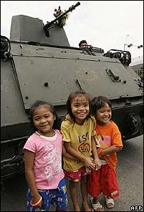 Children pose for a picture in front of a tank in Bangkok
