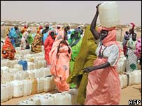 Displaced Sudanese women queue at a water point in Abu Shouk camp, Darfur