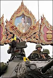 Soldados tailandeses en un tanque pasan por debajo de un arco con un cuadro del rey.