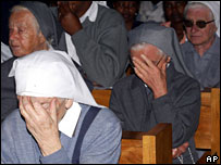 Nuns hold their heads during the ceremony