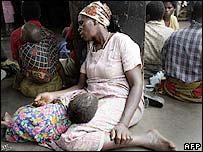 A mother and child wait for food aid in Malawi