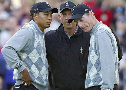 Tiger Woods and Jim Furyk listen intently to the US captain Tom Lehman