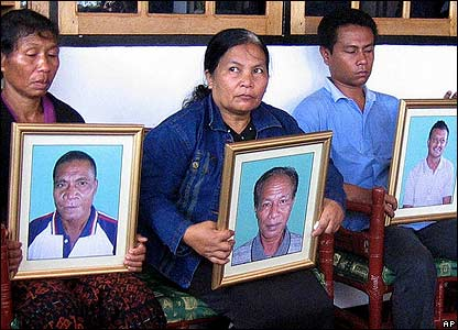 From left to right, Yashinta, wife of Marianus Riwu, Nurlin Kasiala, wife of Fabianus Tibo and Tibo's son Robert, who holds Dominggus Silva's portrait