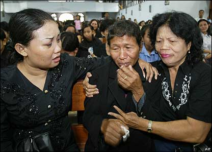 Yashinta, centre, wife of Marianus Riwu comforted by friends at the church