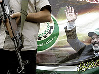 A bodyguard of Palestinian Authority Prime Minister Ismail Haniya holds his weapon next to the PM's poster during a rally in Gaza City