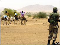 An AU soldier watches Darfurians in Thabit, North Darfur.