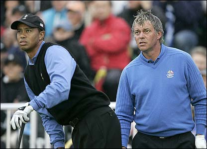 Tiger Woods watches his drive alongside Europe's Darren Clarke