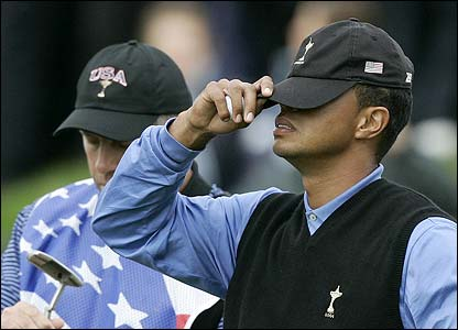 Woods covers his eyes with his baseball cap