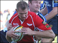 Scarlets wing Dafydd James holds off Denis Hickie to score