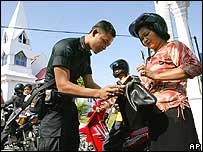 Police officer checks a woman's bag at Poso in Sulawesi