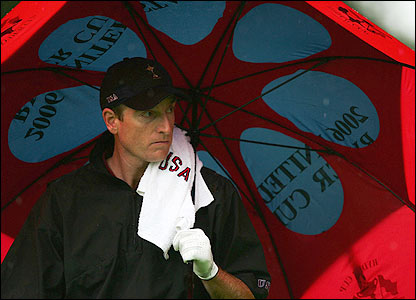 Jim Furyk looks despondent as he shelters from the rain